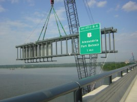 Installing a highway sing on a bridge going over the Potomac river.